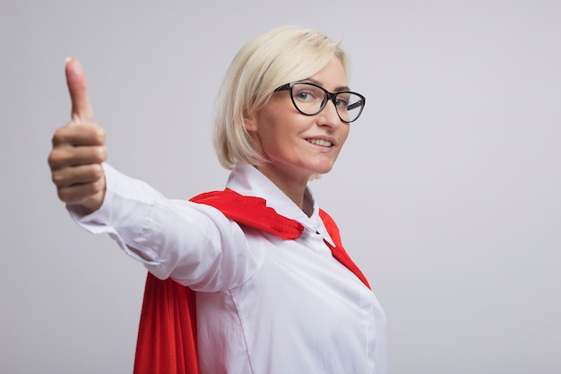Smiling middle-aged blonde superhero woman in red cape wearing glasses standing in profile view  showing thumb up isolated on white wall with copy space
