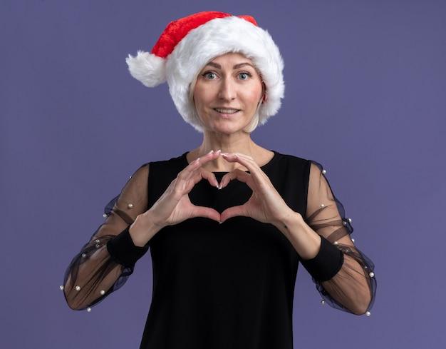 紫色の背景に分離されたハートのサインをやってカメラを見てクリスマス帽子をかぶって笑顔の中年ブロンドの女性