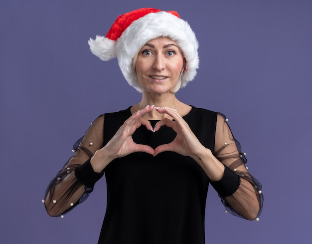 Smiling middle-aged blonde woman wearing christmas hat looking at camera doing heart sign isolated on purple background