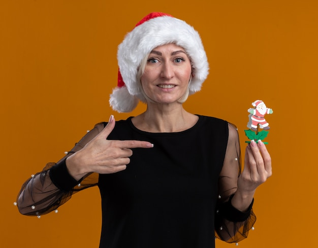 Smiling middle-aged blonde woman wearing christmas hat looking  holding and pointing at santa claus toy isolated on orange wall