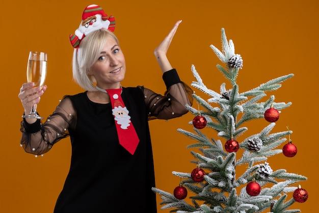 Улыбающаяся блондинка средних лет с ободком и галстуком санта-клауса стоит возле украшенной елки с бокалом шампанского и смотрит, показывая пустую руку, изолированную на оранжевой стене