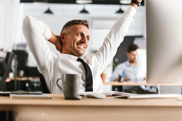 オフィスのテーブルのそばに座ってリラックスして目をそらす中年ビジネスマンの笑顔