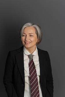회색 배경에 중간 나이 든된 사업가 웃고. 넥타이와 검은 자 켓을 입고 성숙한 회색 머리 백인 여자 광범위 하 게 웃 고 측면에서 보인다. 사업 개념