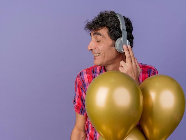コピースペースで紫色の背景に分離された目を閉じてヘッドフォンに触れる風船の後ろに立っているヘッドフォンを身に着けている中年の白人パーティーの男性の笑顔