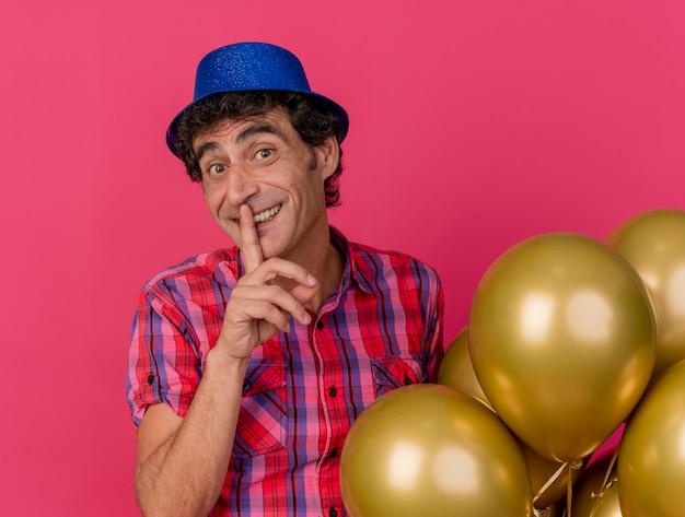 진홍색 배경에 고립 침묵 제스처를 하 고 카메라를보고 풍선을 들고 파티 모자를 쓰고 웃는 중년 백인 파티 남자