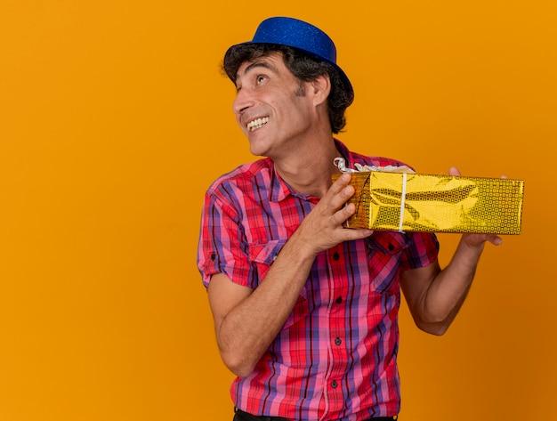 복사 공간 오렌지 배경에 고립 된 측면을 찾고 선물 팩을 들고 파티 모자를 쓰고 웃는 중년 백인 파티 남자