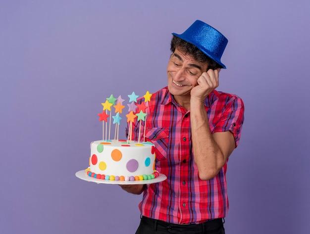 Sorridente uomo caucasico di mezza età del partito che indossa il cappello del partito che tiene e che esamina torta di compleanno che mette la mano sulla faccia isolata su fondo viola con lo spazio della copia
