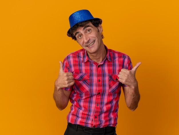 Улыбающийся кавказский тусовщик средних лет в партийной шляпе смотрит в камеру, показывает палец вверх, изолированный на оранжевом фоне с копией пространства