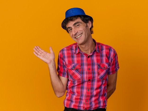 Smiling middle-aged caucasian party man wearing party hat looking at camera showing empty hand keeping another hand behind back isolated on orange background with copy space
