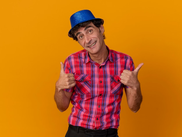 Sorridente uomo caucasico di mezza età del partito che indossa il cappello del partito che guarda l'obbiettivo che mostra i pollici in su isolato su priorità bassa arancione con lo spazio della copia