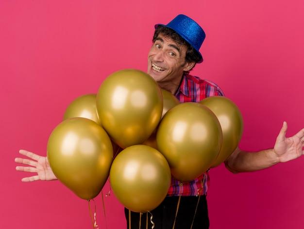 Sorridente uomo caucasico di mezza età che indossa il cappello del partito in piedi dietro i palloncini che guarda l'obbiettivo che mostra le mani vuote isolate su fondo cremisi