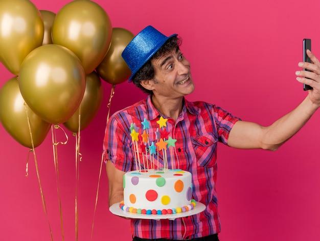진홍색 배경에 고립 된 셀카를 복용하는 생일 케이크를 들고 풍선 근처에 서있는 파티 모자를 쓰고 웃는 중년 백인 파티 남자