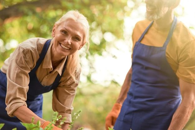 정원에서 일하는 웃는 중년 백인 여성