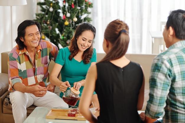 新年を祝うときに家で友達とお茶を飲む中年夫婦の笑顔