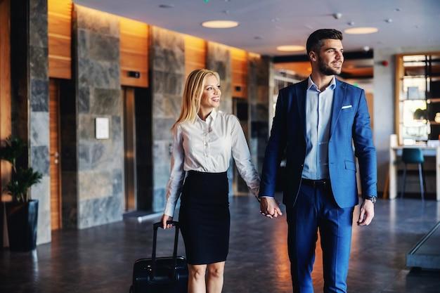 멋진 호텔 로비에서 손을 잡고 걷는 중년 부부 미소. 그들은 그들의 방으로 들어갑니다. 여자가 가방을 당기고있다.