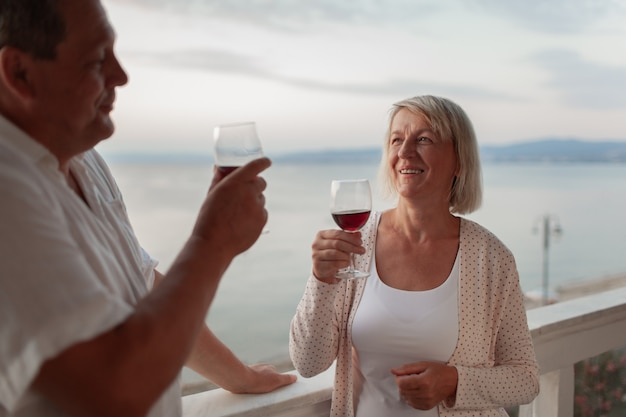 A smiling middle aged couple on a terrace close to the sea