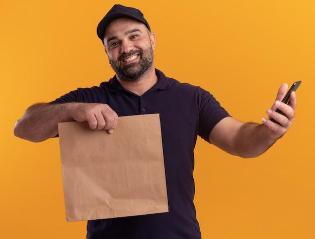 노란색 벽에 고립 된 전화와 종이 음식 패키지를 들고 유니폼과 모자에 중년 배달 남자 미소
