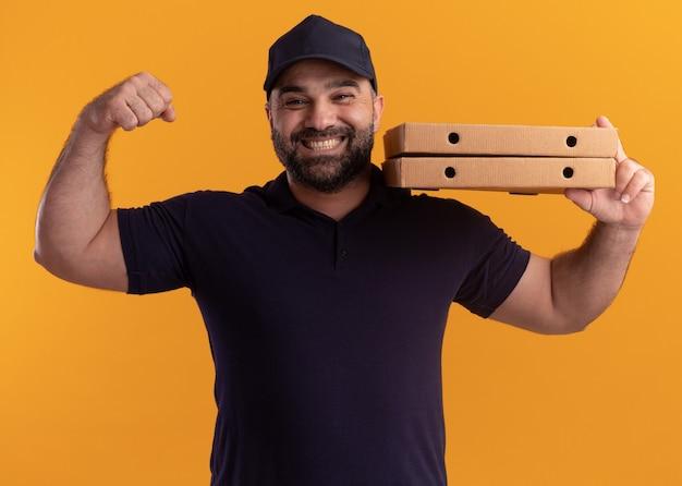 Улыбающийся курьер среднего возраста в униформе и кепке держит коробки с пиццей на плече, показывая сильный жест, изолированный на желтой стене