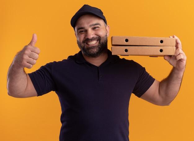 Улыбающийся курьер среднего возраста в униформе и кепке, держащий коробки для пиццы на плече, показывает большой палец вверх изолированным на желтой стене