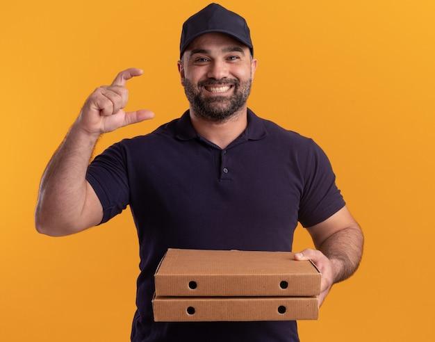 Улыбающийся курьер среднего возраста в униформе и кепке держит коробки для пиццы, показывая размер, изолированные на желтой стене