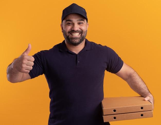 Улыбающийся курьер среднего возраста в униформе и кепке, держащий коробки для пиццы, показывает палец вверх изолированным на желтой стене