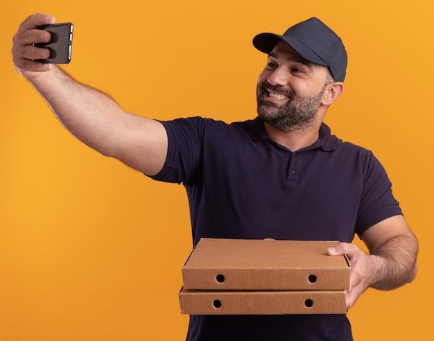 균일 한 중년 배달 남자 웃 고 피자 상자를 들고 모자 노란색 벽에 고립 된 셀카 걸릴