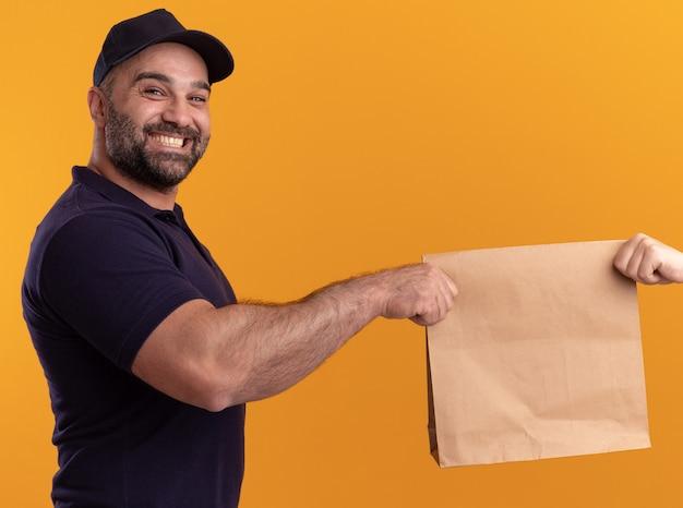 Uomo di consegna di mezza età sorridente in uniforme e cappuccio che dà il pacchetto di cibo di carta al cliente isolato sulla parete gialla