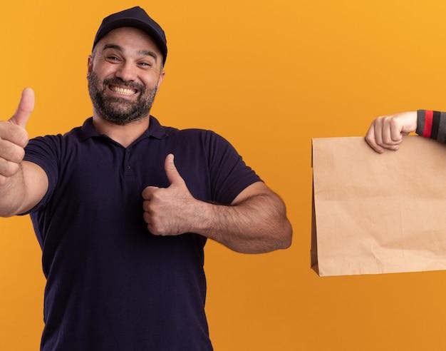 Uomo di consegna di mezza età sorridente in uniforme e cappuccio che dà il pacchetto di cibo di carta al cliente che mostra il pollice su isolato sulla parete gialla