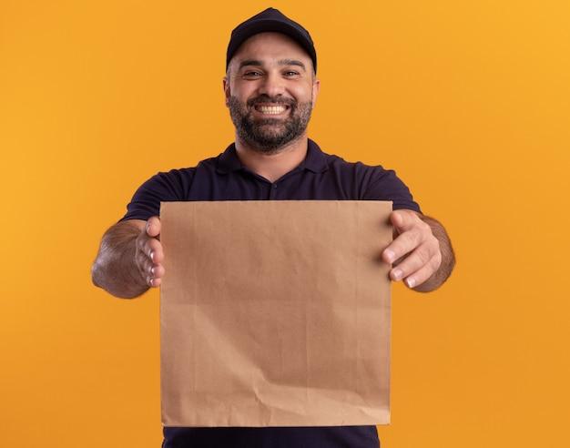 Uomo di consegna di mezza età sorridente in uniforme e cappuccio che tiene fuori il pacchetto di cibo di carta nella parte anteriore isolata sulla parete gialla