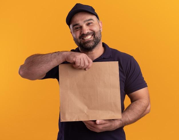 Uomo di consegna di mezza età sorridente in uniforme e cappuccio che tiene il pacchetto di cibo di carta isolato sulla parete gialla