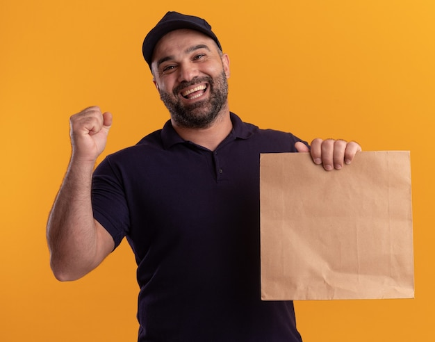 Smiling middle-aged delivery man in uniform and cap holding paper food package showing yes gesture isolated on yellow wall
