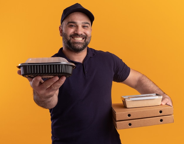Smiling middle-aged delivery man in uniform and cap holding pizza boxes and holding out food container  isolated on yellow wall