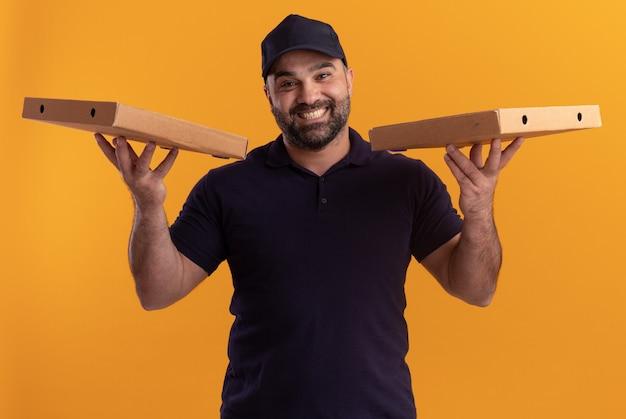 Uomo di consegna di mezza età sorridente in uniforme e cappuccio che tiene le scatole per pizza isolate sulla parete gialla