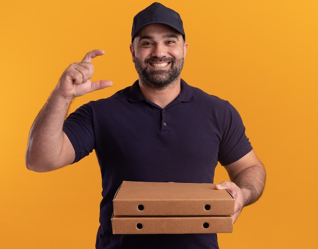 Smiling middle-aged delivery man in uniform and cap holding pizza boxes showing size isolated on yellow wall