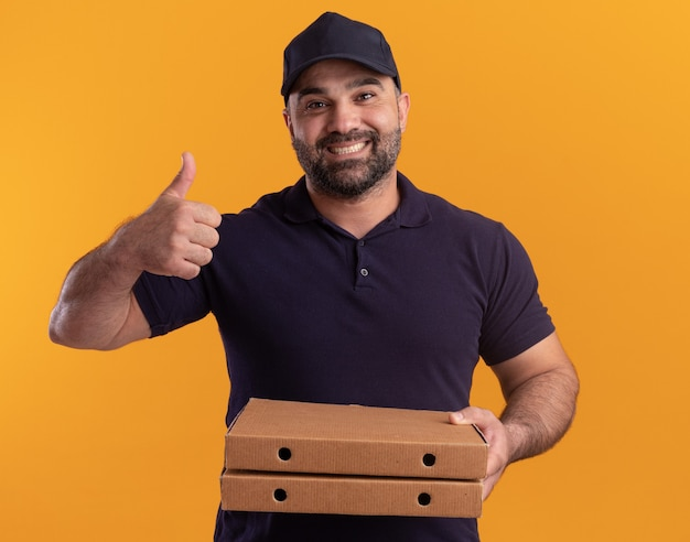 Smiling middle-aged delivery man in uniform and cap holding pizza boxes showing thumb up isolated on yellow wall