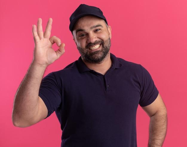 Uomo di consegna di mezza età sorridente in uniforme e cappuccio che mostra gesto giusto isolato sulla parete rosa