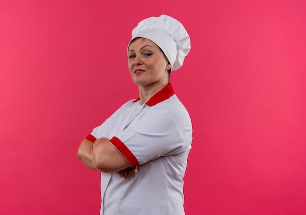 Cuoco femminile di mezza età sorridente nelle mani dell'incrocio dell'uniforme del cuoco unico con lo spazio della copia