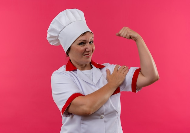Smiling middle-aged female cook in chef uniform doing strong gesture