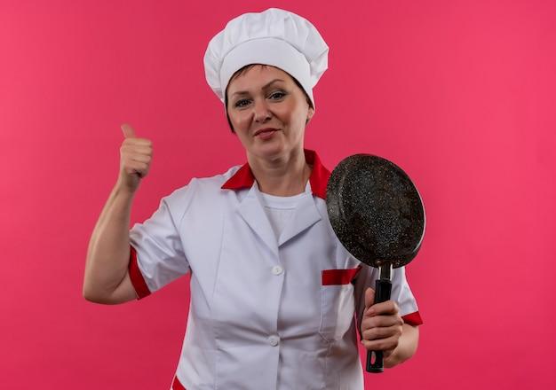 Cuoco femminile di mezza età sorridente in uniforme del cuoco unico che tiene la padella il suo pollice in su
