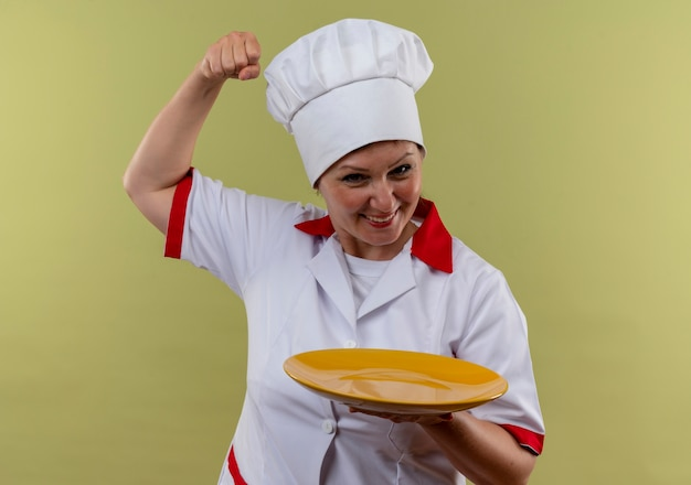 Smiling middle-aged female cook in chef uniform holding plate doing strong gesture  with copy space