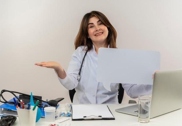 의료 가운과 청진기를 입고 의료 도구 클립 보드와 노트북이 고립 된 빈 손을 보여주는 채팅 거품을 들고 책상에 앉아 웃는 중년 여성 의사