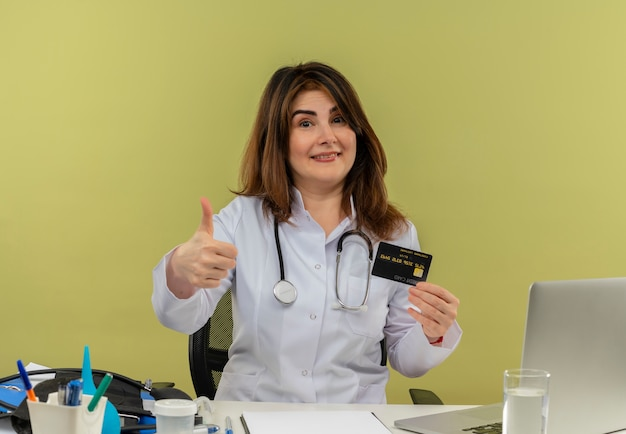Smiling middle-aged female doctor wearing medical robe and stethoscope sitting at desk with medical tools and laptop holding credit card showing thumb up isolated
