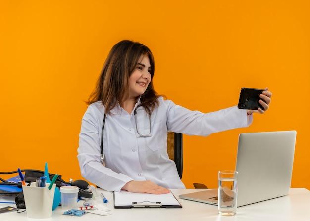 Улыбающаяся женщина-врач средних лет в медицинском халате со стетоскопом, сидя за столом, работает на ноутбуке с медицинскими инструментами, делает селфи на изолированном оранжевом фоне с копией пространства