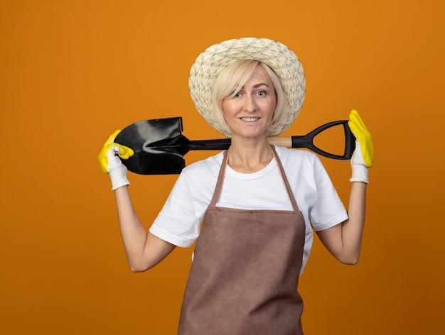 Sorridente giardiniere di mezza età donna in uniforme da giardiniere che indossa cappello e guanti da giardinaggio tenendo la vanga dietro il collo guardando la telecamera isolata su sfondo arancione