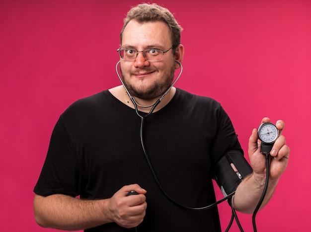 ピンクの壁に分離された血圧計で自分の圧力を測定する笑顔の中年の病気の男性