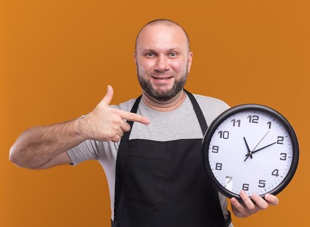 Sorridente barbiere maschio di mezza età in tenuta uniforme e indica l'orologio da parete isolato su parete arancione