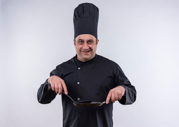 Cuoco maschio di mezza età sorridente in uniforme del cuoco unico che tiene padella e spatola