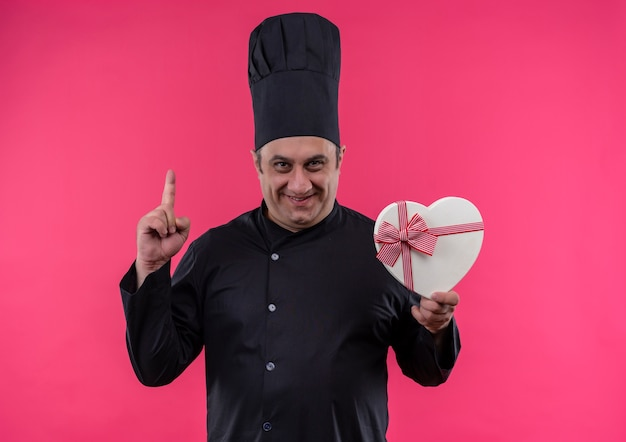 Smiling middle-aged male cook in chef uniform holding heart shape box points finger up