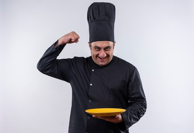 Smiling middle-aged male cook in chef uniform holding plate showing strong gesture