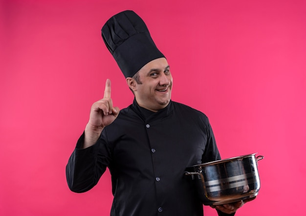 Il cuoco maschio di mezza età sorridente nella casseruola uniforme della tenuta del cuoco unico punta il dito verso l'alto con lo spazio della copia
